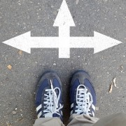 Male sneakers on the asphalt road with drawn direction arrow